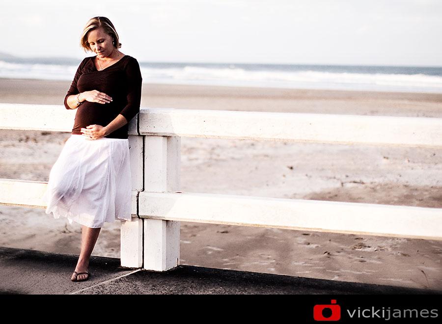 pregnant lady leaning against bridge rail