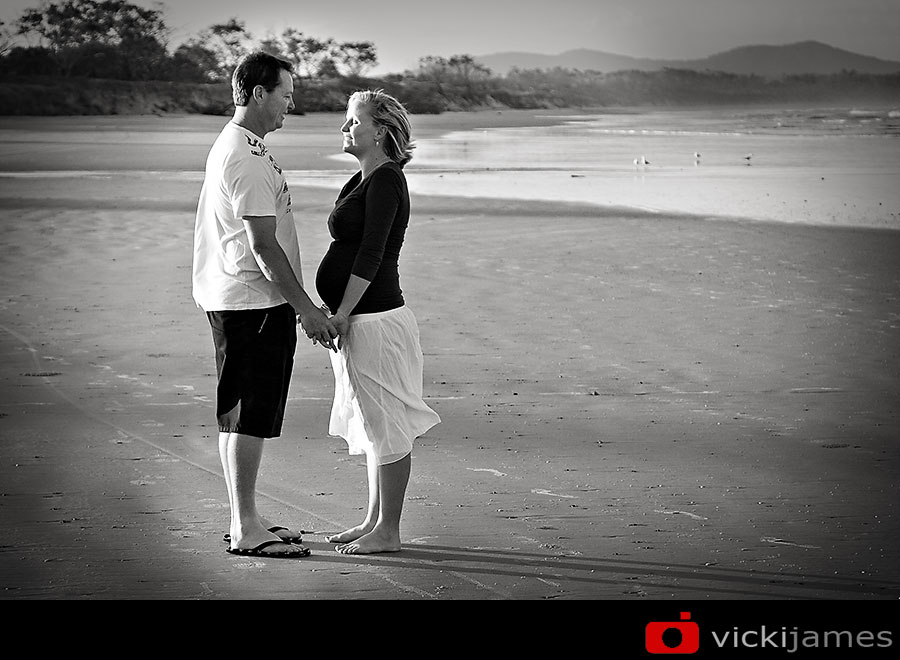 pregnant lady  and man standing on a beach holding hands