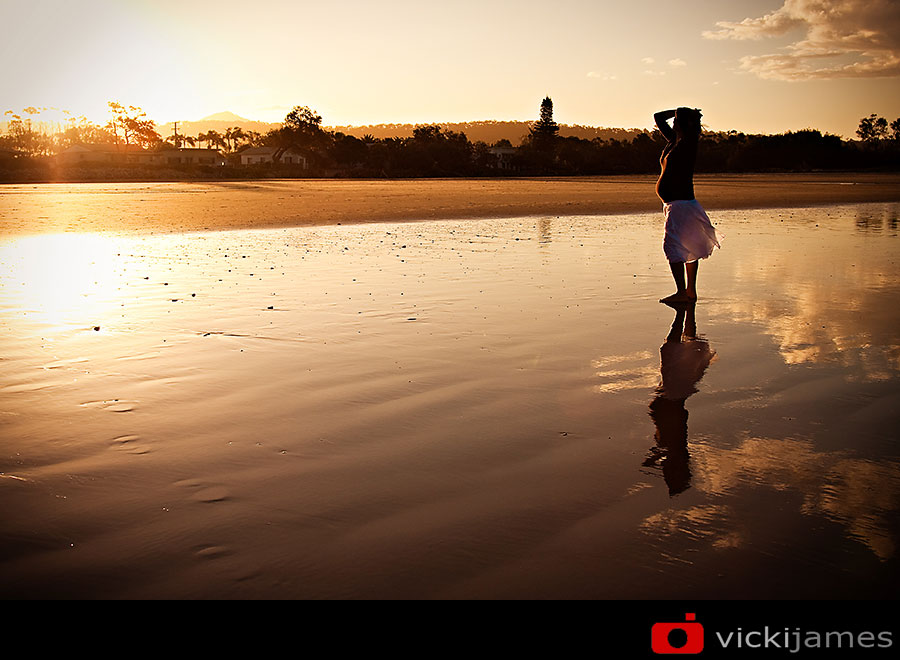 pregnant lady standing on a beach at sunset