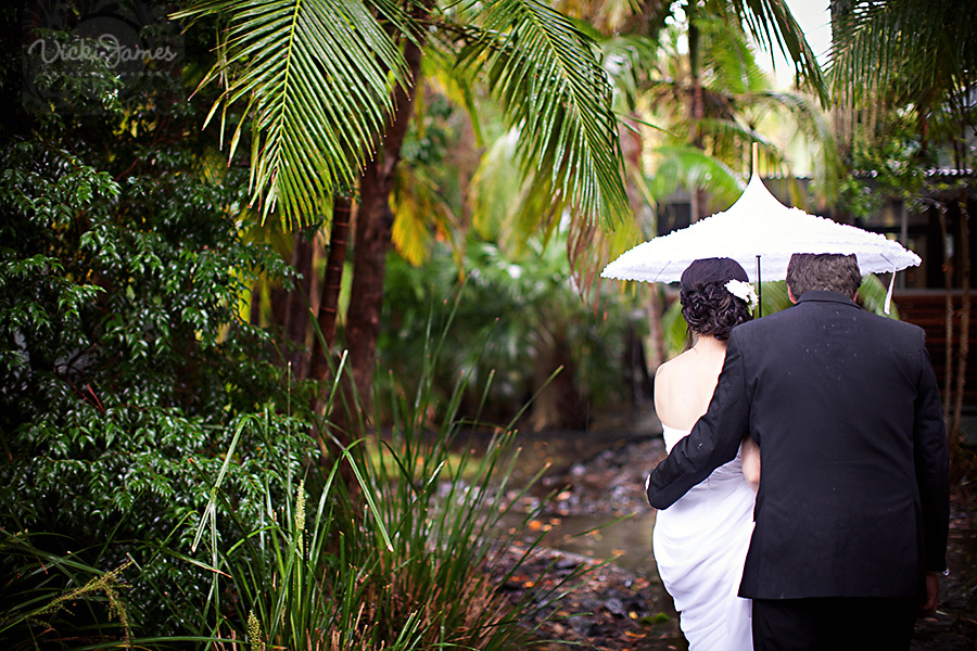 Yamba Wedding Photographer, Bride and Groom huddled under umbrella