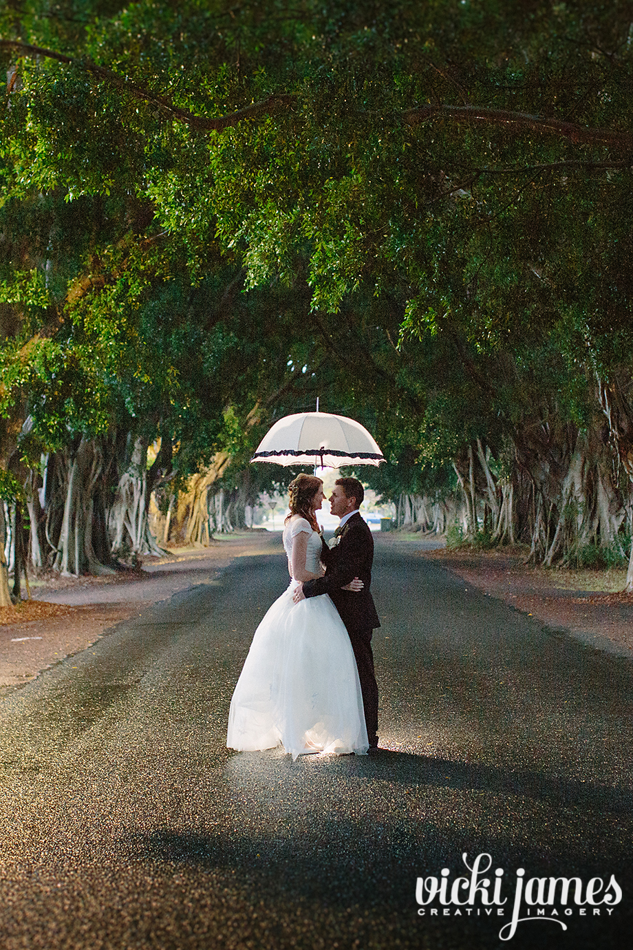 bride and grrom under umbrella in the rain