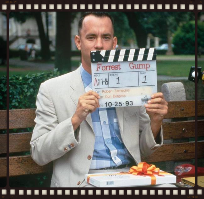 Tom Hanks sitting on the famous Forrest Gump bench that was created in Hollywood and shipped in for the movie. This is scene one, act one as the slate says. The actual bench was placed on Chippewa Square where the Chippewa Square sign now stands. The lighting was between trees so it was consistent for the shot. The square was shot down for 4 days to get the bench scenes for the movie.