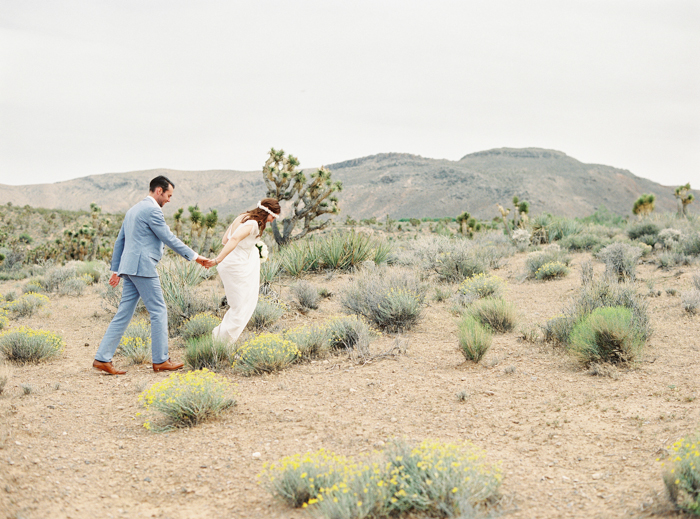 bride and groom walking through las vegas desert wildflower patch