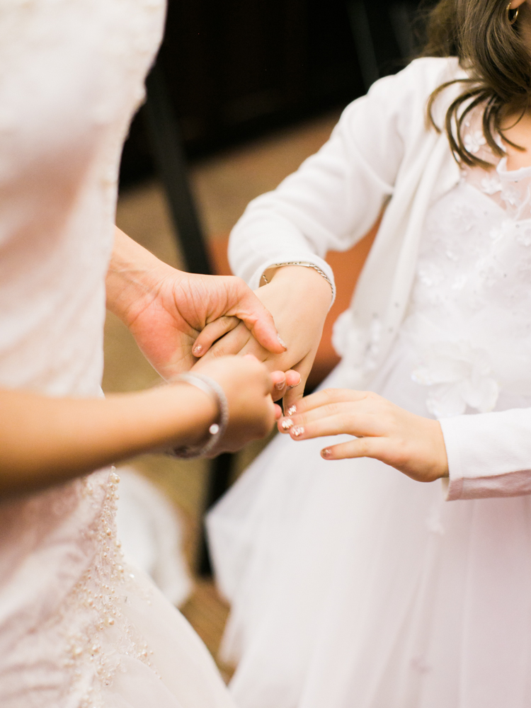 bride holding hands with the flower girl