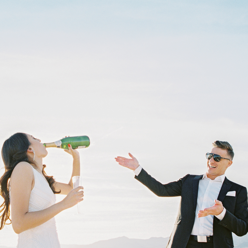 bride drinking champagne out of bottle