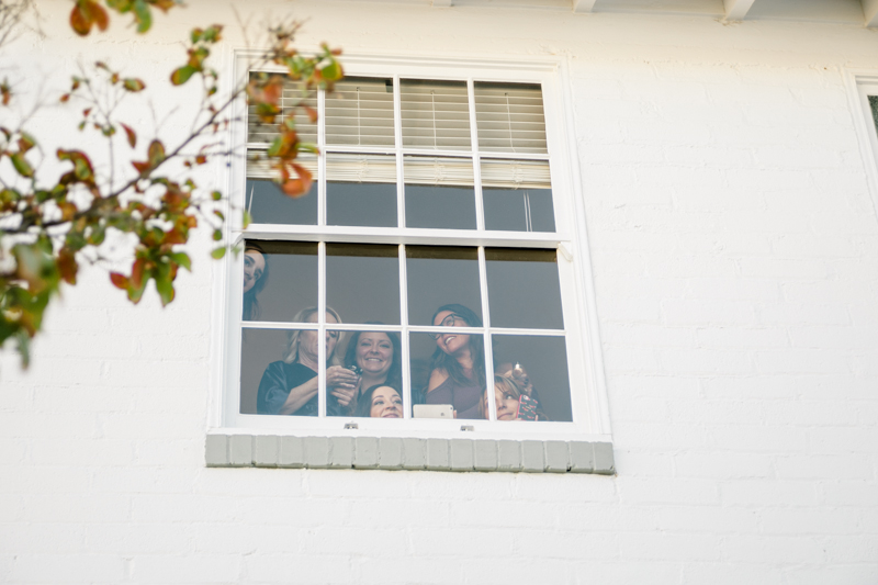 wedding party looking through window