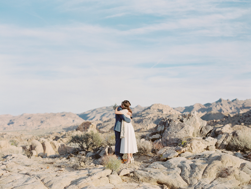 bride and groom hugging each other in the desert