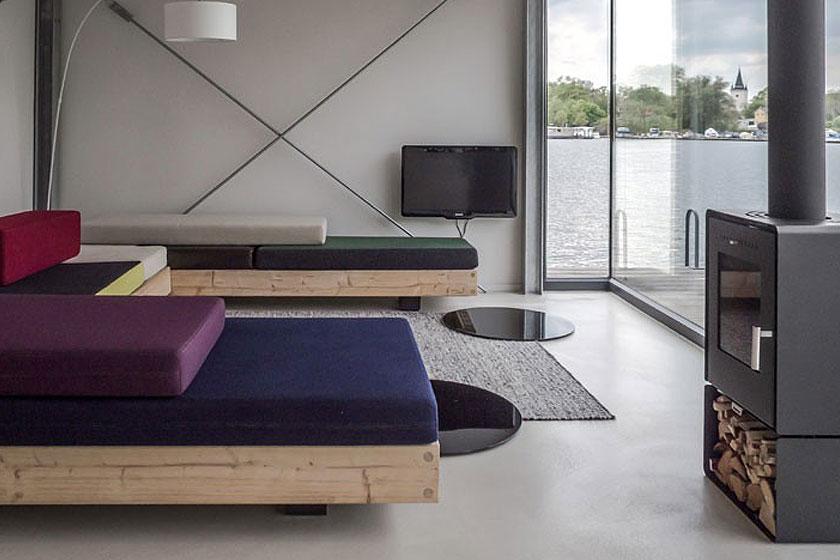 Hotel woonboot in Berlijn.De op maat gemaakte houten bank in de huiskamer kan ook dienen als slaapplaats voor extra gasten.
