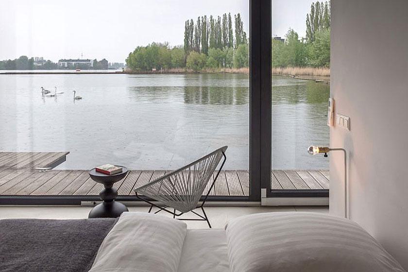 Hotel woonboot in Berlijn. De slaapkamer met eenvoudig design interieur overziet de rivier en het meer van Rummelsburg.