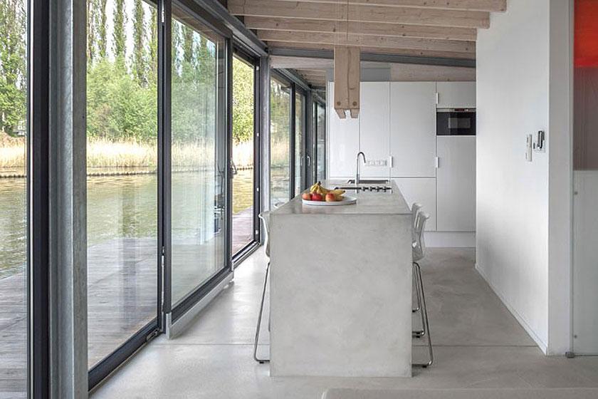 Het betonnen kookeiland siert de industriële keuken op de woonboot in Berlijn.