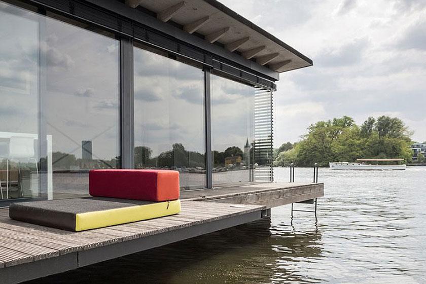 Het interieur van de bijzondere woonboot loopt door tot op een houten dek. Perfect om voorbijzwemmende zwanen te spotten. Het dok ligt vlakbij een natuurreservaat.