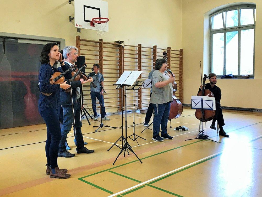 Die Schulleiterin der Primarschule Triemli, Frau Idil Calis stellt das Projekt Camerata@School vor. Projekt Kick-Off: Musik liegt in der Luft: Eine Turnhalle voller Lebensfreude!