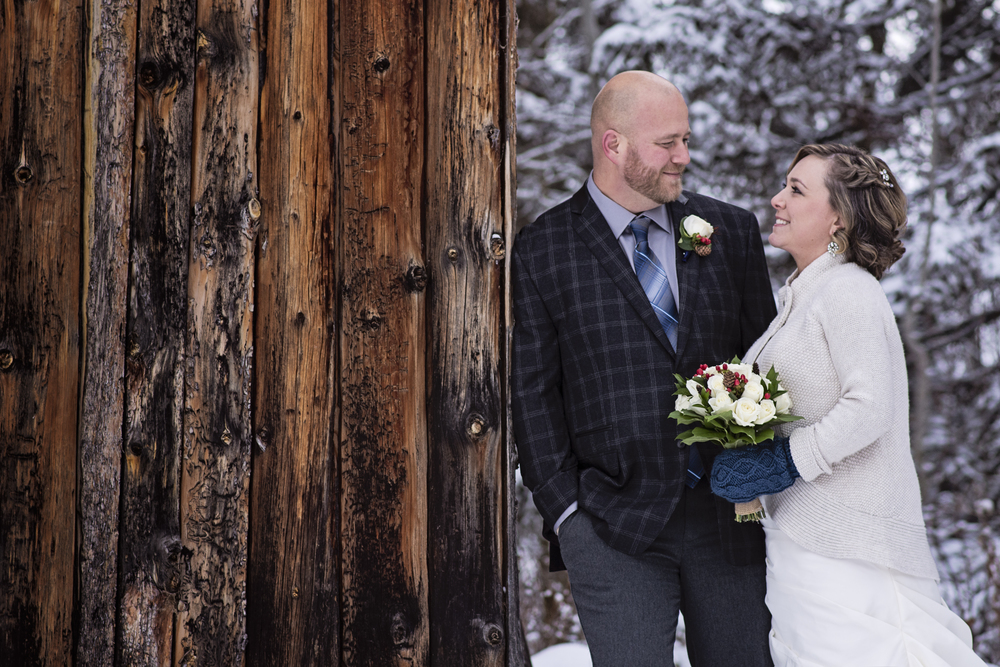 Winter Bride and Groom beside an old wood barn