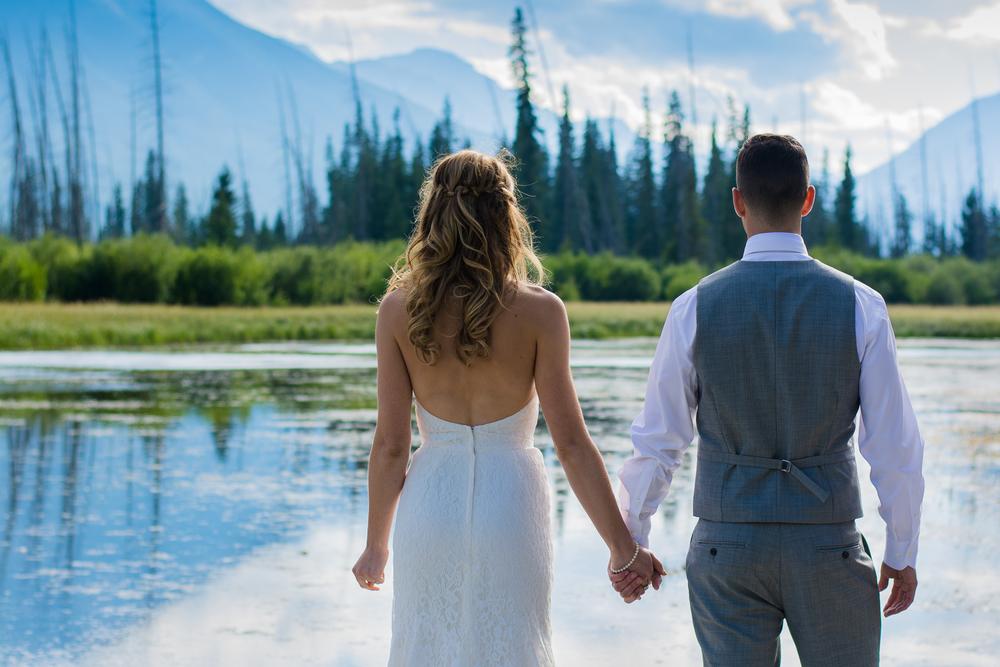 Bride and Groom holding hands facing Vermilion Lakes, Banff, Alberta, Canada