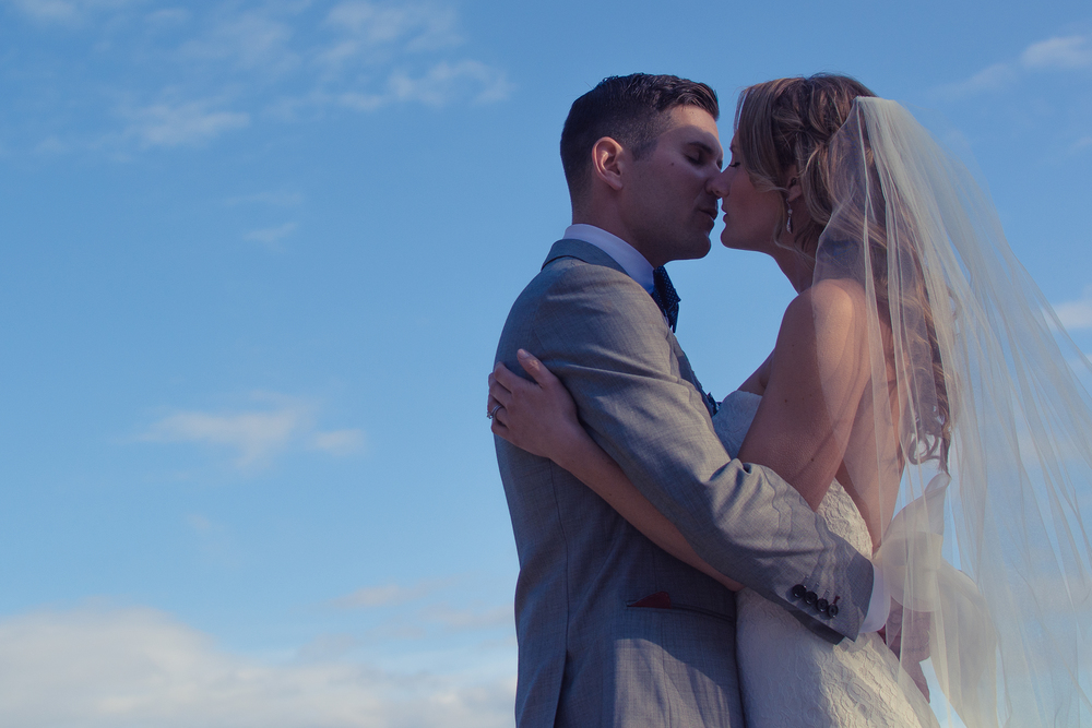 Bride and Groom kissing in the clouds