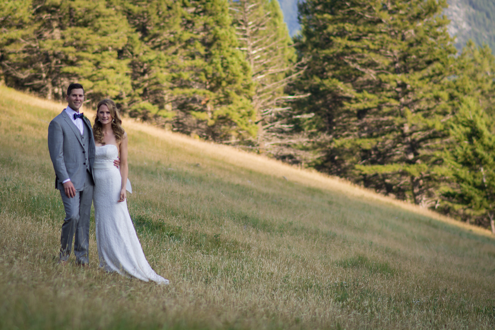 Bride and Groom standing on a sharp grassy hill