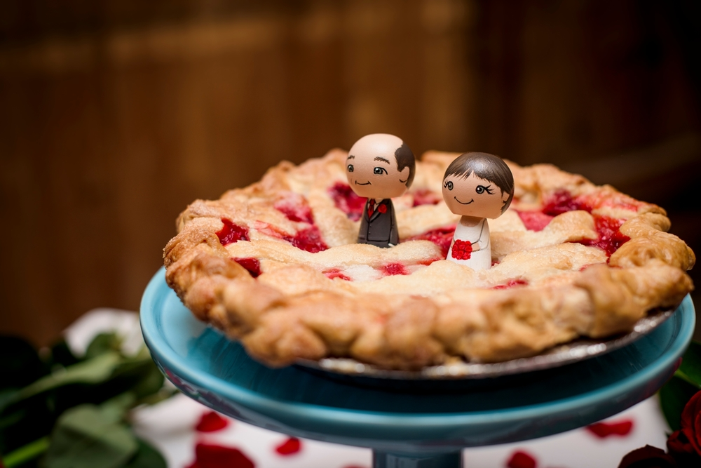 baked pie with bride and groom figurines on top
