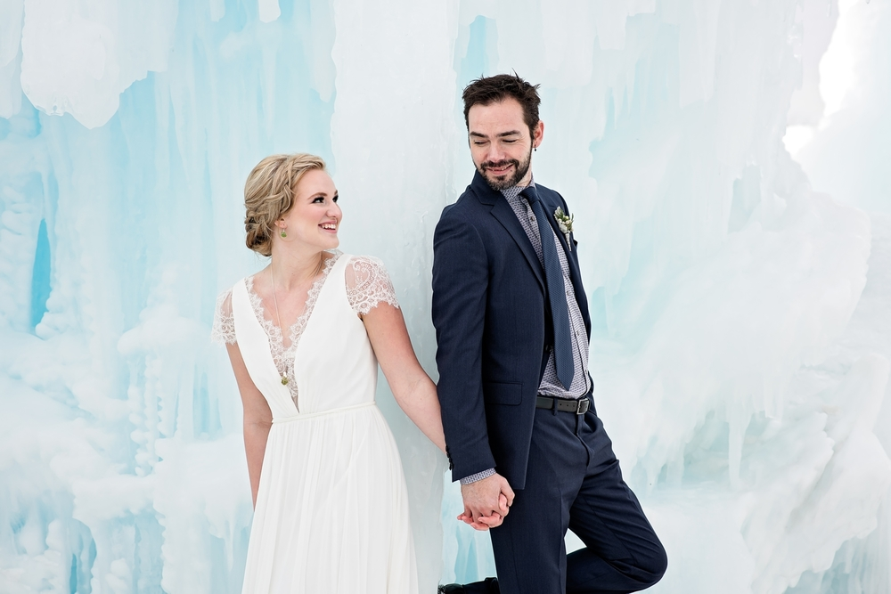 Married wedding bride and groom in an ice castle holding hands and smiling