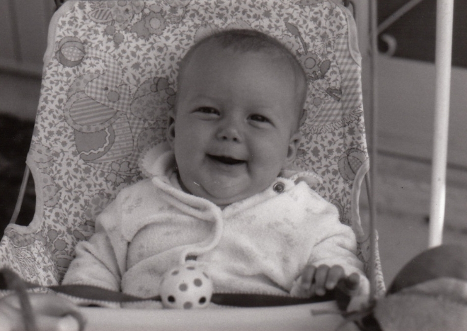 This is a chunky baby version of myself smiling.