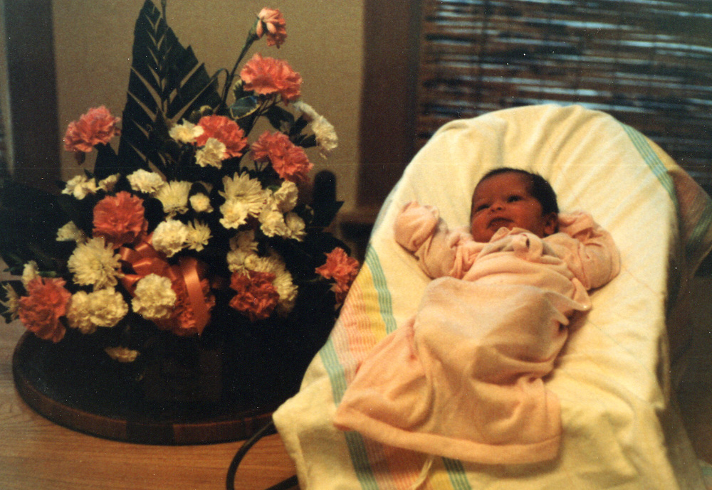 048 in gown next to flowers - 2-3 months.jpg
