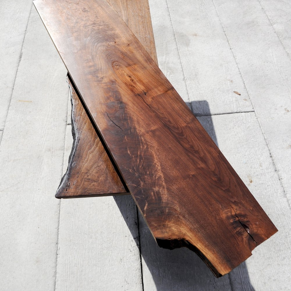 Coffee Table - Natural edged walnut from a tree that had been struck by lightening is supported by a folded metal structure, suspending the planks above one another.A custom mechanism enables the wood to reconfigure, expanding the table and contracting it, when necessary.