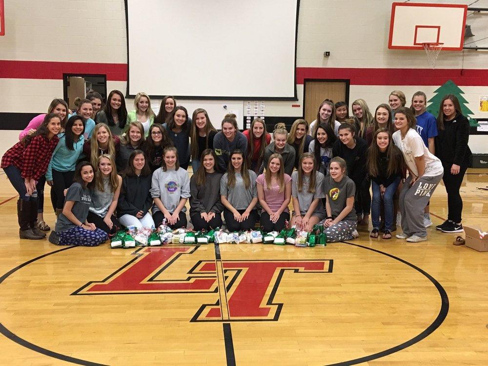 Junior varsity and varsity cheerleaders display their gift bags for Mobile Meals of Lake Travis.