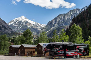Ouray RV Park and Cabins - Ouray RV Park & Cabins is 7.5 acres of beautiful river front that runs along the Uncompaghre River, surrounded with breathtaking mountain views. We are located 1/2 mile north of downtown Ouray on Hwy. 550, and just a short riverwalk from the Hot Springs Pool, and the quaint shops and restaurants.We offer a diverse range of riverfront cabins, tent sites and full hook up (50/30/20 amp/water/sewer) RV sites. Additional amenities include a beautiful heated bathhouse, laundry facilities and a TV/Game room that is open 24 hours daily. Ouray Cafe (our onsite restaurant open to the public) has 3 big screen TVs, daily Happy Hour specials and offers both breakfast and dinner. Ice Park Members receive 10% off their cabin, tent or RV site booking!