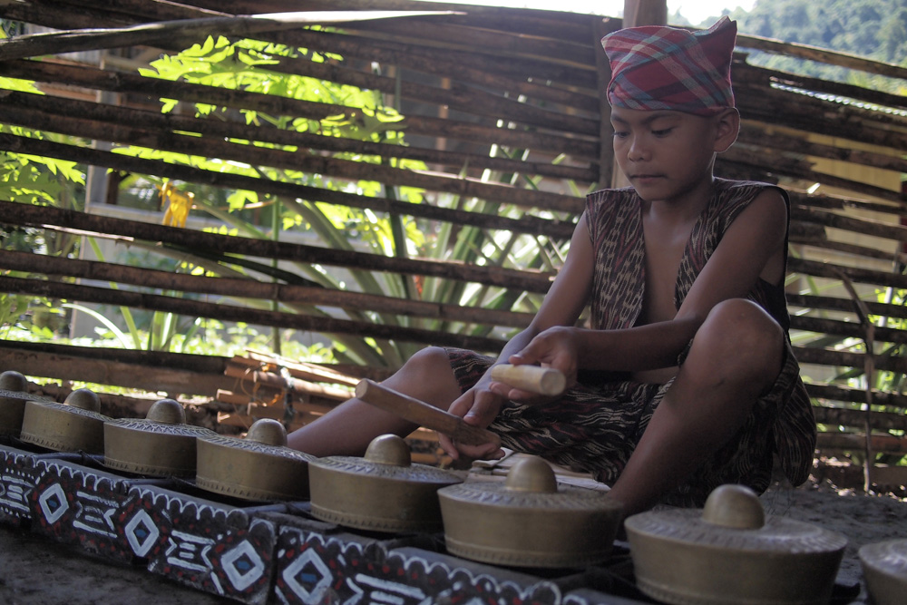 A T'boli youth plays the kulintang, a brass percussion instrument