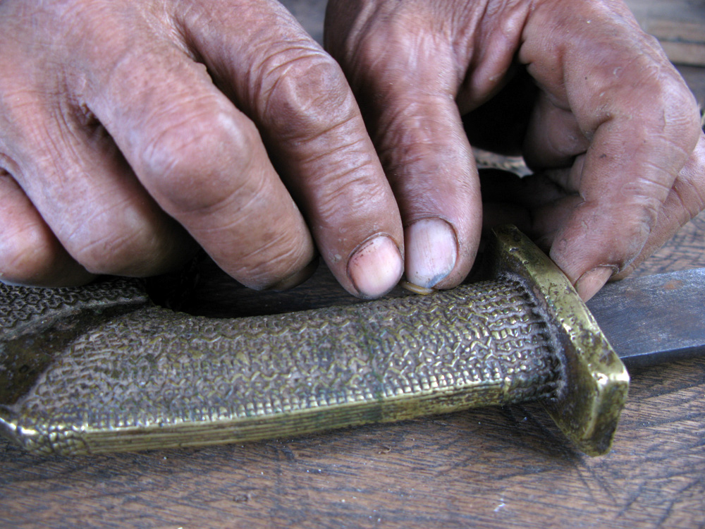 Semblang demonstrates how wax is formed to make the design in this sword handle