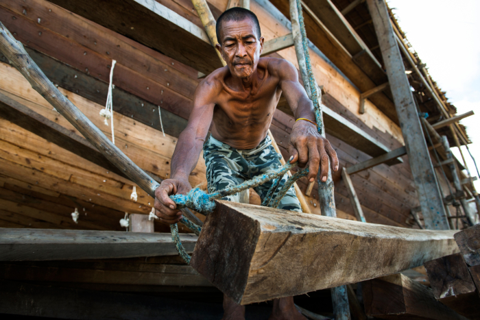 A shipbuilder prepares to latch a rope around a wooden beam to be hoisted inside the hull of the vessel.