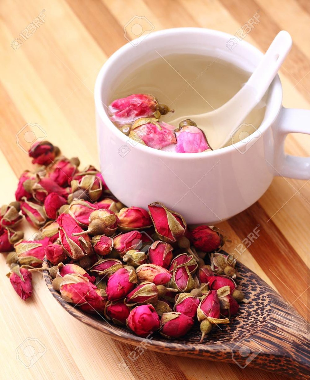 23556433-dried-roses-wooden-scoop-and-a-cup-of-rose-tea-on-simple-background.jpg