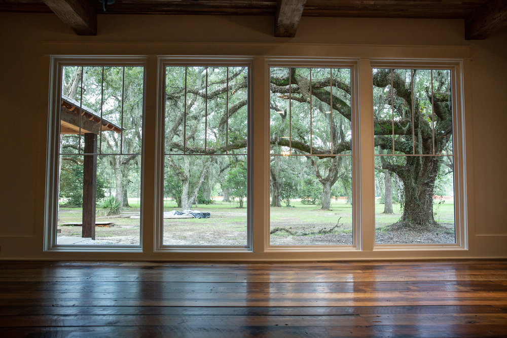 Floor-to-ceiling windows frame a stand of majestic live oaks—a reminder that despite its ingenious design flourishes, this Creole cottage is right at home in South Louisiana.