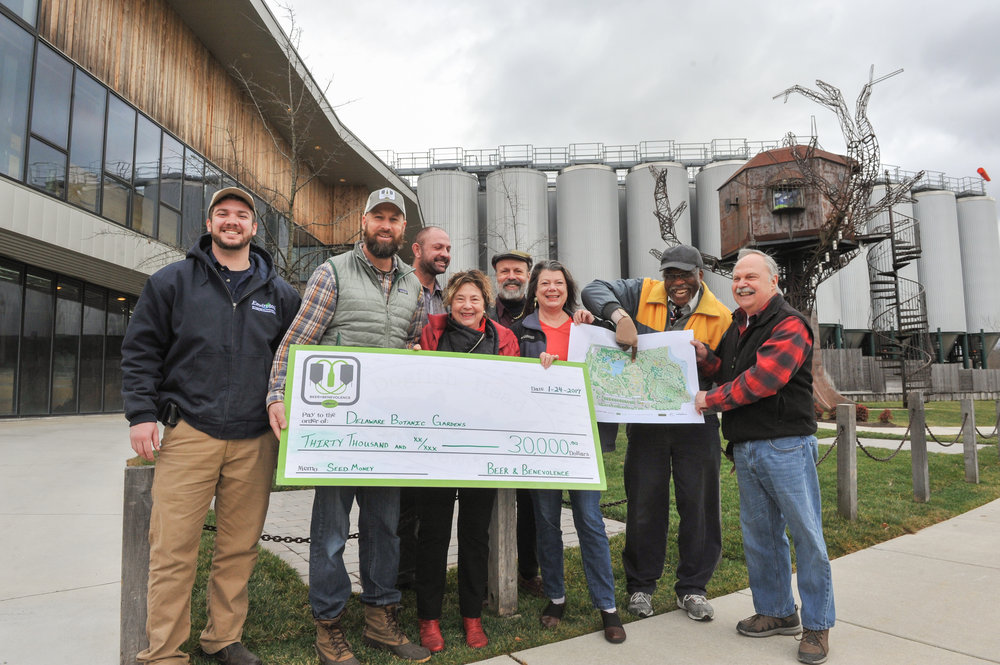 Mark Carter (second from left), director of Dogfish Head's Beer & Benevolence program, presents the company's $30,000 pledge to the Delaware Botanic Gardens at the brewery in Milton. Tyler Hammond, director of operations for Envirotech Environmental Consulting, is at the far left. They are joined by DBG leaders (from left) Gregg Tepper, Sheryl Swed, Henry DeWitt, Janet Point, Peter Carter, and Raymond Sander. Photo courtesy Dogfish Head Companies