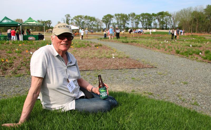 Piet Oudolf, internationally acclaimed Dutch garden designer, sits on one of the mounds he had built in his meadow creation at the Delaware Botanic Gardens in Dagsboro. He said the grassed mound allows visitors to get at the level of the plants and see the meadow from a different perspective. CHRIS FLOOD PHOTO