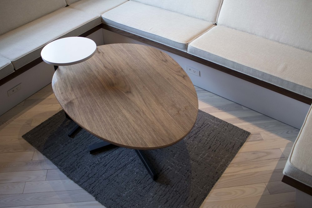 The is a walnut ply egg shape coffee table with metal base. On the left, white side table with metal base.