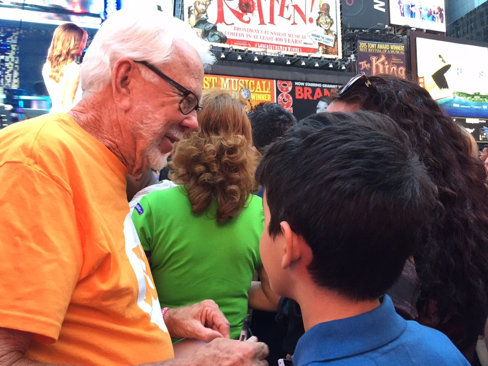 Norm Miller (Interstate Batteries) counsels a young family in Times Square.