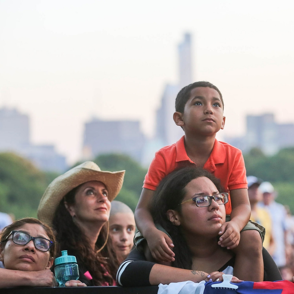 Families listen to Luis' message in Central Park on July 11.