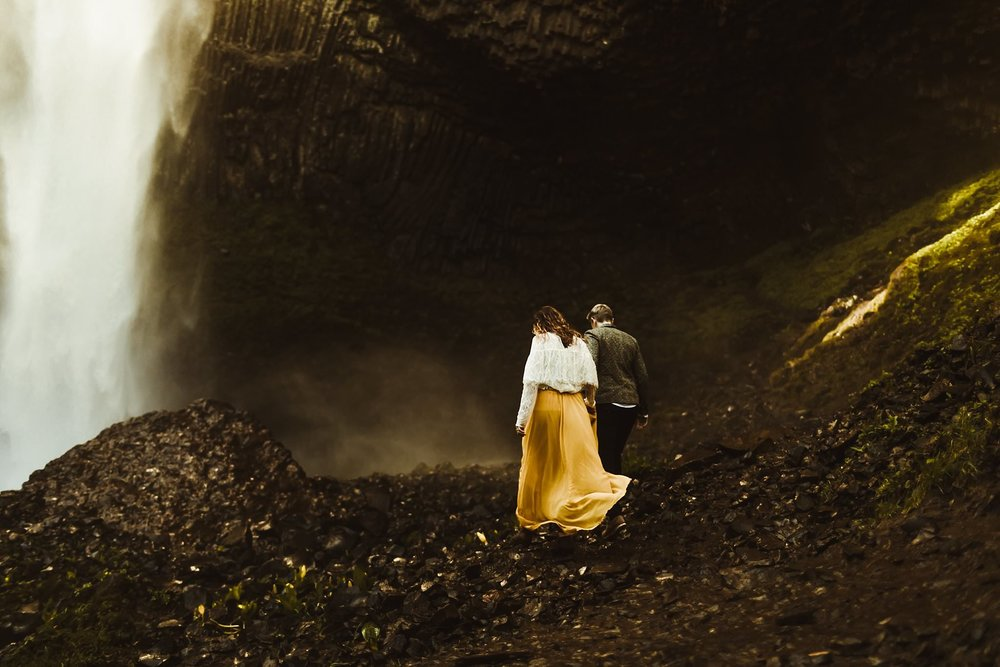 A same-sex couple hiking to a waterfall for their elopement photos