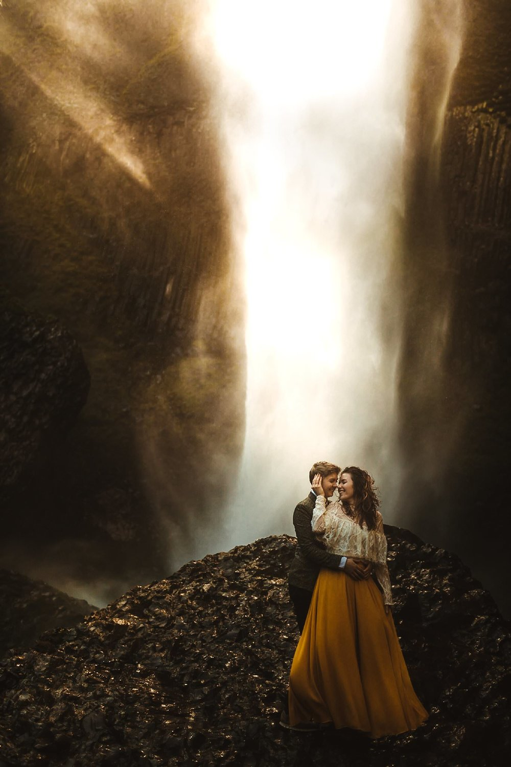 A same-sex couple standing underneath the Latourell Falls for their elopement