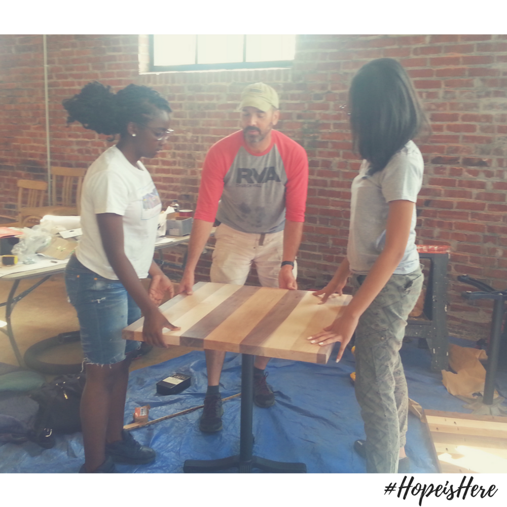 Imani, Erika, and Volunteer Kevin install table at the Front Porch Cafe