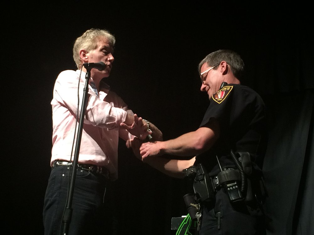 Greatest Living Escape Artist Michael Griffin gets locked up by Police Officer during a stage demonstration of his escape powers
