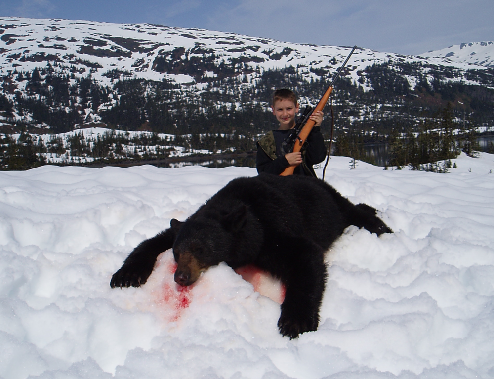 "My grandson Nathan Juliussen age 10 with his 6'5"" bear.  It was taken about 25 yards from where Jared shot his first bear.  Nathan was the youngest to take a bear."