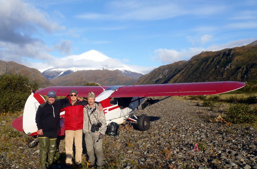 Clients and guides alike loved flying with Gary.  Here he is with guide Mike Warner on the left and client Gary Young on the right. The Chiginagak Volcano is in the background.
