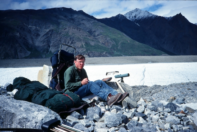 Ron sitting close to camp studying the cliff mountain.
