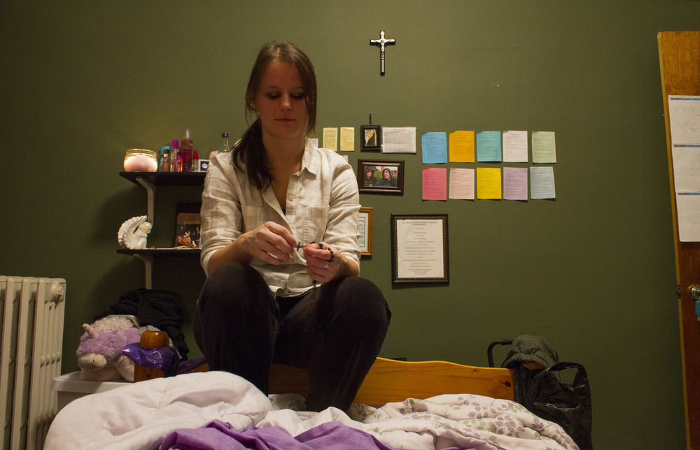 Catholic Minister Melissa McChesney, 24, holds rosary beads before evening prayers.