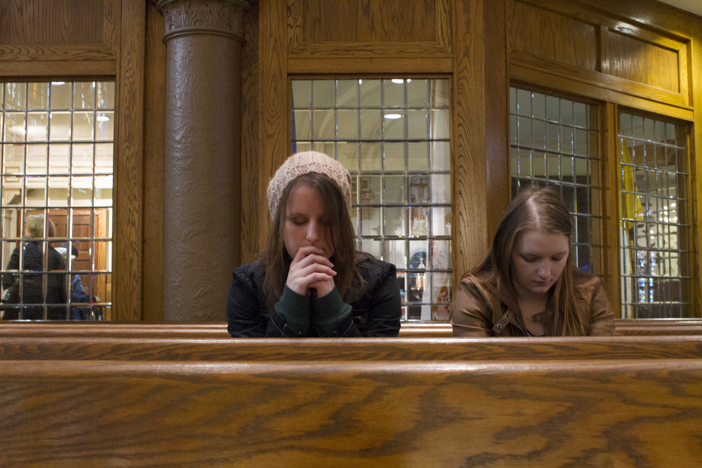 Catholic Minister Melissa McChesney, 24, prays at noon mass with her sister.