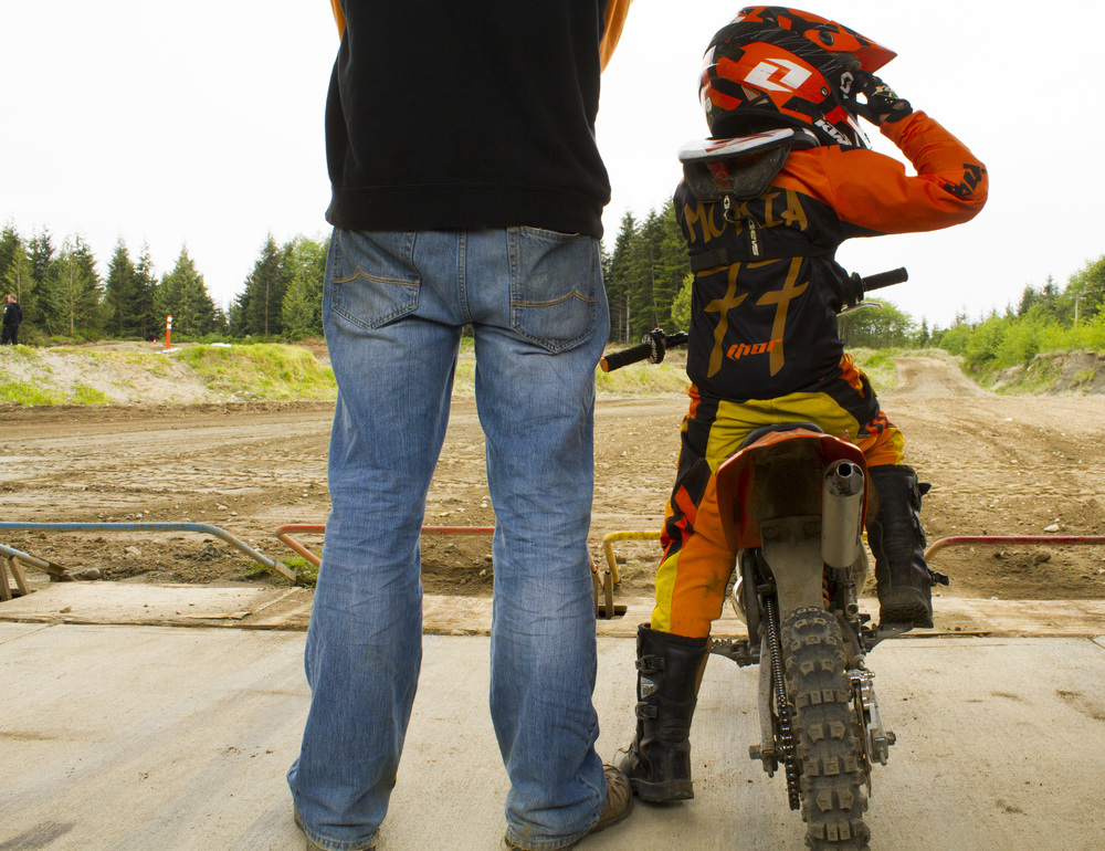 A boy and his father wait for a motocross race near Port McNeill, B.C.  © North Island Gazette.