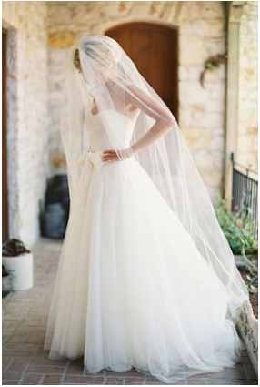 Bride in a ballroom gown with chapel length veil.