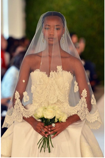 Bride with a lace trimmed fingertip length veil.