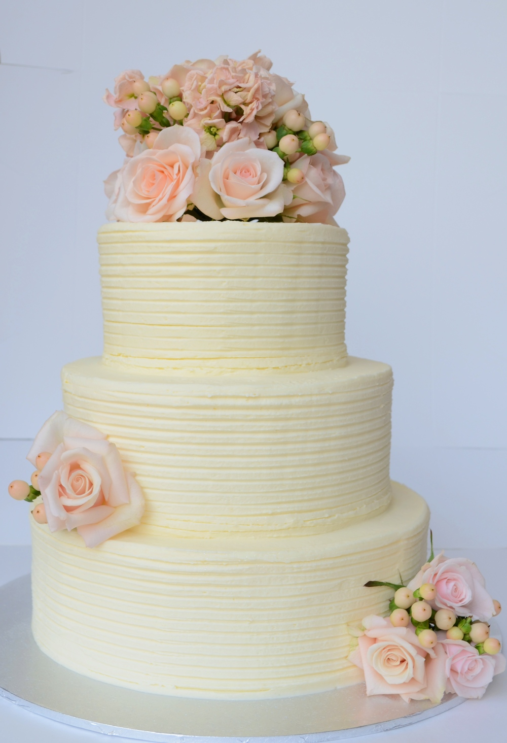 Vanilla Pod Frosted Wedding Cake. White chocolate mud with lemon mousse cake with textured scrape finish and fresh flowers.JPG